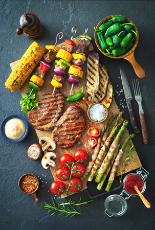 Barbecue menu. Grilled meat and vegetables on rustic stone plate