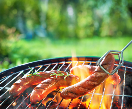 Grilled sausages on grill with smoke and flame on a meadow. Barbecue picnic Stock Photo