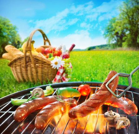 Grilled sausages on grill und picnic basket on a meadow Stock Photo