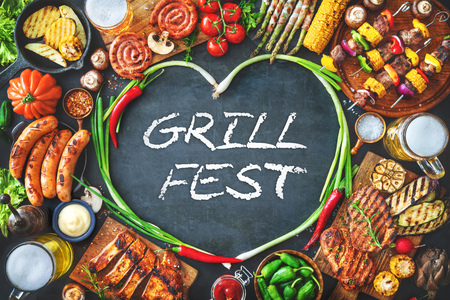 Barbecue menu. Grilled meat and vegetables on rustic stone plate with copy space for text