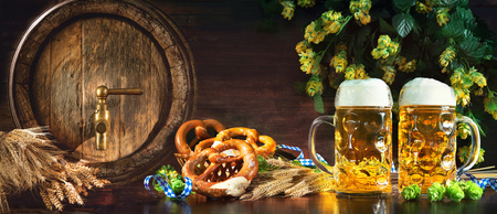 Oktoberfest beer barrel and beer glasses with soft pretzels, wheat and hop on rustic wooden table