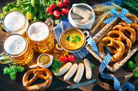 Bavarian sausages with pretzels, sweet mustard and beer mugs on rustic wooden table. Oktoberfest menu Stockfoto