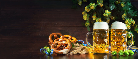 Bavarian beer with soft pretzels, wheat and hop on rustic wooden table. Oktoberfest background