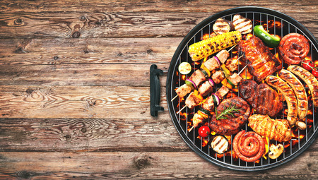 Assorted delicious grilled meat and bratwurst with vegetables over the coals on a barbecue on rustic wooden background Stock Photo