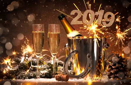 New Years Eve celebration background with pair of flutes and bottle of champagne in  bucket  and a horseshoe as lucky charm Фото со стока - 101761817