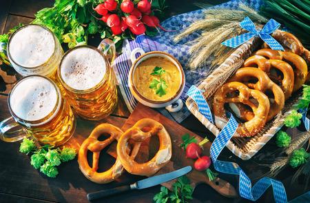 Bavarian beer with soft pretzels, obatzter and radish on rustic wooden table. Oktoberfest menu Stock Photo