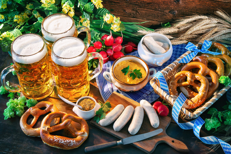Bavarian sausages with pretzels, sweet mustard and beer mugs on rustic wooden table. Oktoberfest menu Stock Photo