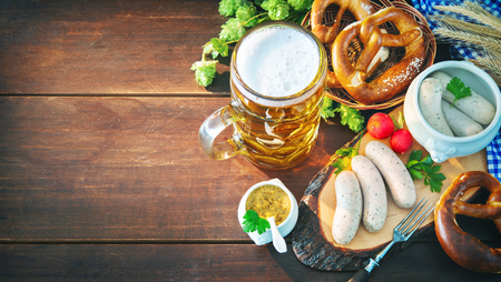Bavarian sausages with pretzels, sweet mustard and beer mug on rustic wooden table. Oktoberfest menu Stock Photo