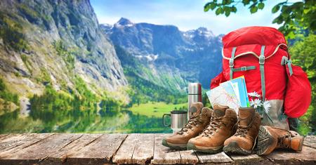 paisaje del lago con mochila grande y botas de trekking en las montañas Foto de archivo
