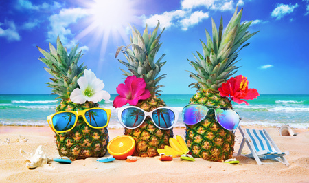 Attractive pineapples in stylish sunglasses on the sand against turquoise sea. Tropical summer vacation concept