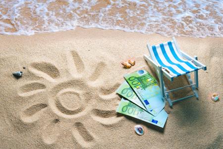 Deckchair with euro bills on a beach with a sun drawn on the sand. Travel money savings concept