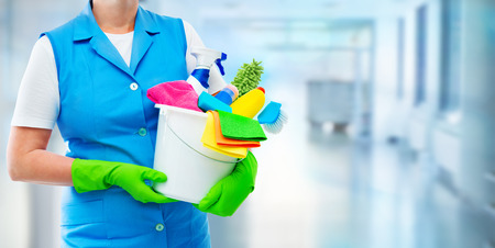 Female housekeeper while cleaning office. Woman wearing protective gloves and holding bucket full of cleaning supplies on blurred background