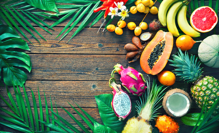 Assortment of tropical fruits with leaves of palm trees and exotic flower on dark wooden background. Top view Stock Photo