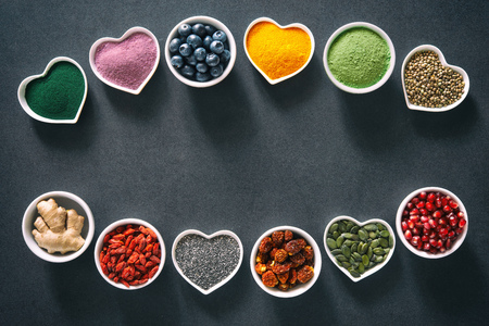 Various colorful superfoods as acai powder, turmeric, matcha green tea, spirulina, quinoa, pumpkin seeds, blueberry, dried goji berries, cape gooseberries, raw cocoa, hemp seeds and other in bowls on dark background