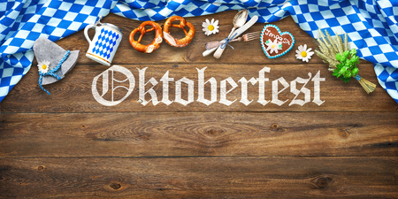 Rustic background for Oktoberfest with white and blue fabric, Bavarian hat, hop, gingerbread, beer stein and pretzel on wooden table