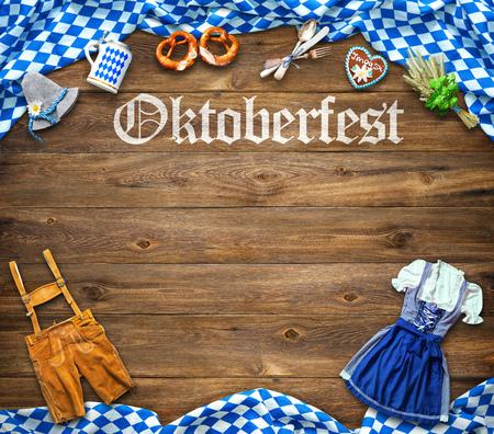 Rustikaler Hintergrund für Oktoberfest mit weißem und blauem Stoff, bayerischer Kleidung, Lebkuchen, Bierkrug und Brezel Standard-Bild