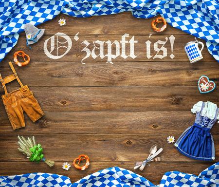Rustikaler Hintergrund für Oktoberfest mit weißem und blauem Stoff, bayerischer Kleidung, Lebkuchen, Bierkrug und Brezel