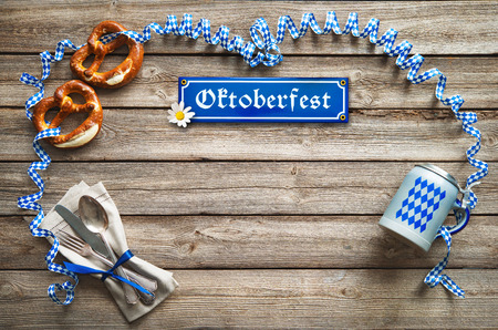 Rustic background for Oktoberfest with Bavarian white and blue streamer, pretzel, bier stein and silverware Stock Photo