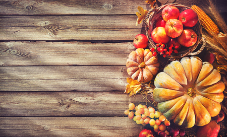Thanksgiving background with pumpkins, corn cobs, fruits, wheat and falling leaves on rustic wooden table Standard-Bild - 106999437