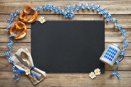 Rustic background for Oktoberfest with Bavarian white and blue streamer, pretzel, bier stein and silverware Foto de archivo - 106999444