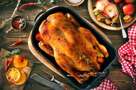 Roast Christmas duck with thyme and apples on rustic wooden table Foto de archivo - 107317156