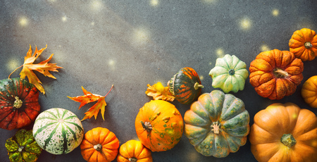 Thanksgiving background with various pumpkins, gourds and falling leaves on rustic dark table Foto de archivo - 107317139