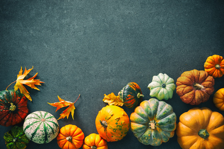 Thanksgiving background with various pumpkins, gourds and falling leaves on rustic dark table Foto de archivo - 107317144