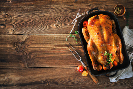 Roast Christmas duck with thyme and apples on rustic wooden table Foto de archivo - 107317145