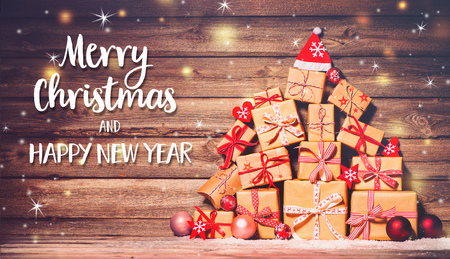 Christmas background with decorations and gift boxes on wooden board with Merry Chtistmas and Happy New Year text Foto de archivo - 108473317