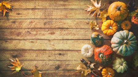 Thanksgiving pumpkins with fruits and falling leaves on rustic wooden table Foto de archivo - 108473318