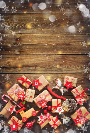 Christmas background with decorations and gift boxes on wooden board Foto de archivo - 108473319