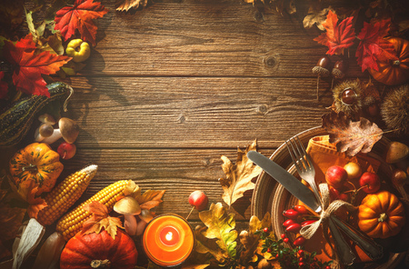 Autumn background from fallen leaves, fruits with vintage place setting and burning candle on old wooden table. Thanksgiving day concept Foto de archivo - 108473320