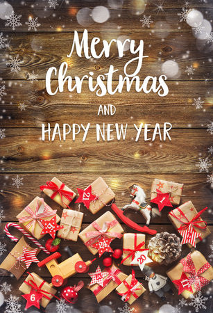 Christmas background with decorations and gift boxes on wooden board with text Merry Chtistmas and Happy New Year Foto de archivo - 108582660