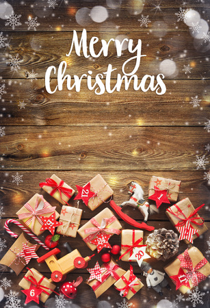 Christmas background with decorations and gift boxes on wooden board with Merry Chtistmas text Foto de archivo - 108582659