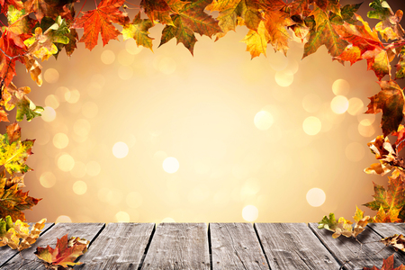 Autumn background with falling leaves on wooden plank