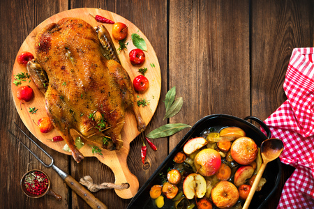 Roast Christmas duck with thyme and apples on rustic wooden table Foto de archivo - 108968326