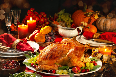 Thanksgiving dinner. Roasted turkey garnished with cranberries on a rustic style table decoraded with pumpkins, vegetables, pie, flowers and candles Foto de archivo - 108968329
