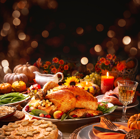 Thanksgiving dinner. Roasted turkey garnished with cranberries on a rustic style table decoraded with pumpkins, vegetables, pie, flowers and candles Foto de archivo - 108968331