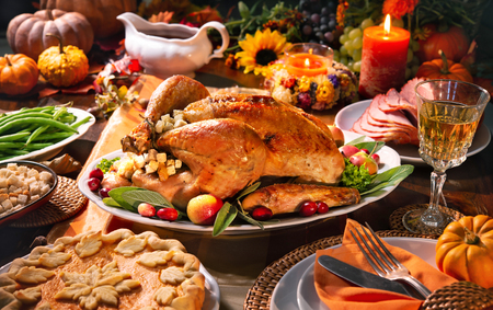 Thanksgiving dinner. Roasted turkey garnished with cranberries on a rustic style table decoraded with pumpkins, vegetables, pie, flowers and candles Foto de archivo - 108968332