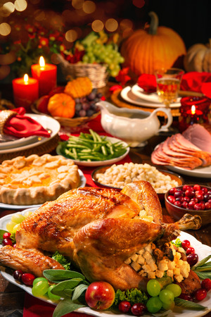 Thanksgiving dinner. Roasted turkey garnished with cranberries on a rustic style table decoraded with pumpkins, vegetables, pie, flowers and candles Foto de archivo - 108968334