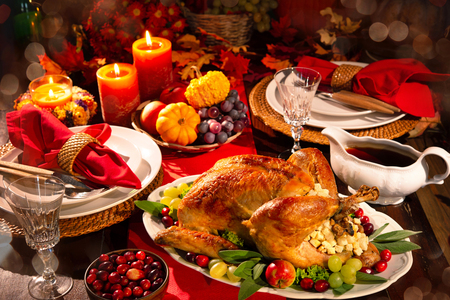 Thanksgiving dinner. Roasted turkey garnished with cranberries on a rustic style table decoraded with pumpkins, vegetables, pie, flowers and candles Foto de archivo - 108968337