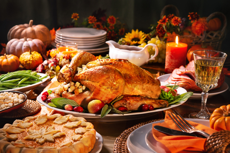 Thanksgiving dinner. Roasted turkey garnished with cranberries on a rustic style table decoraded with pumpkins, vegetables, pie, flowers and candles Foto de archivo - 108968341