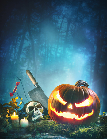 Jack o' lantern glowing at moonlight in front of spooky forest. Halloween background