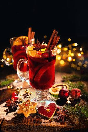 Christmas mulled red wine with spices and fruits on a wooden rustic table. Traditional hot drink at Christmas time Foto de archivo - 109828111
