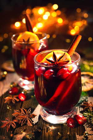 Christmas mulled red wine with spices and fruits on a wooden rustic table. Traditional hot drink at Christmas time Foto de archivo - 109828113