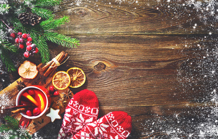 Christmas mulled red wine with spices and fruits on a wooden rustic table. Traditional hot drink at Christmas time Foto de archivo - 109828115