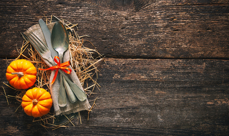 Autumn background from pumpkins and wheat with vintage place setting on old wooden table. Thanksgiving day concept Foto de archivo - 110353032
