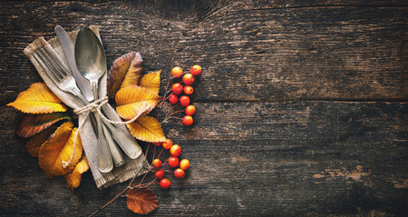 Autumn background from fallen leaves and fruits with vintage place setting on old wooden table. Thanksgiving day concept Foto de archivo - 110353033