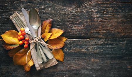 Autumn background from fallen leaves and fruits with vintage place setting on old wooden table. Thanksgiving day concept Foto de archivo - 110353034