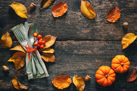 Autumn background from fallen leaves and fruits with vintage place setting on old wooden table. Thanksgiving day concept Foto de archivo - 110353038